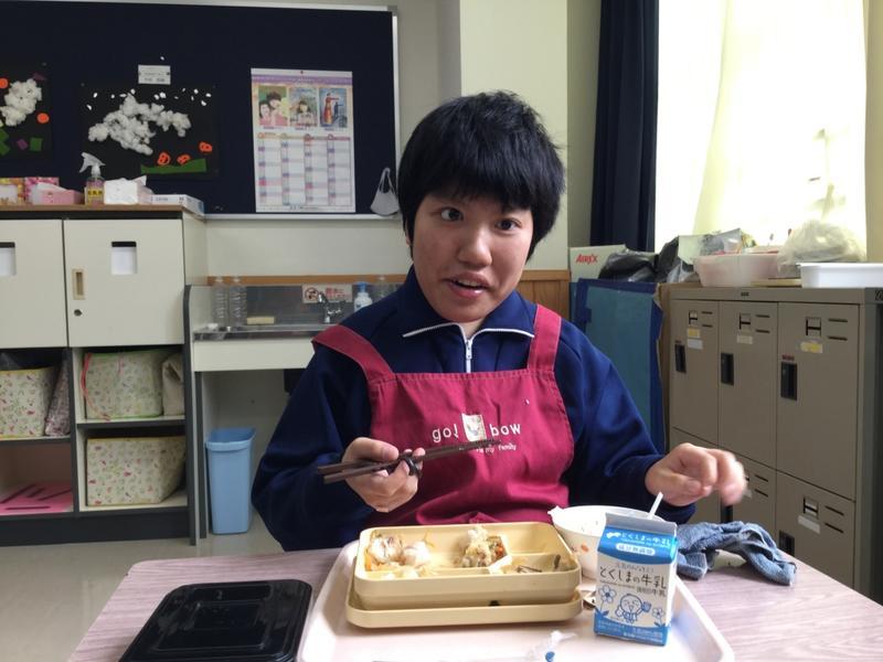 笑顔で給食を食べる生徒