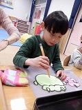 幼児がクレヨンで鬼の顔に線を書いているところ
