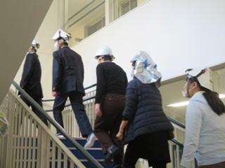 ヘルメットをかぶり、屋上に避難しています